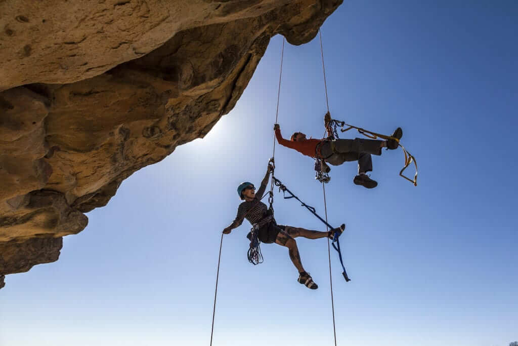 Couple top-rope climbing on a rock face