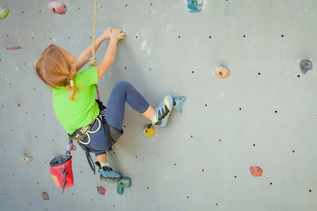 Young girl on rock climbing wall