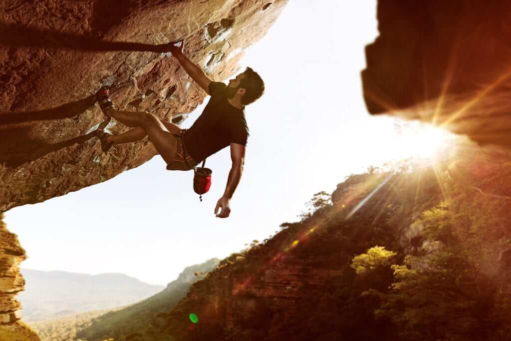 Man bouldering on a large boulder