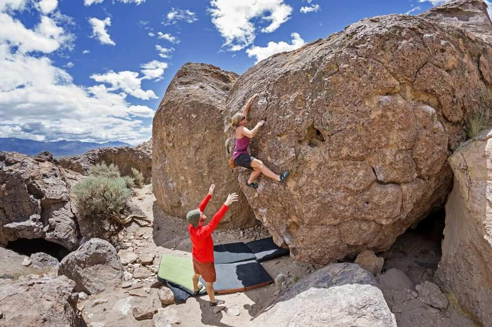 Bouldering with a spotter in the outdoors.